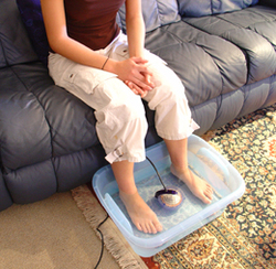 Refer a Friend Gal on couch with Feet in foot tub and orb
